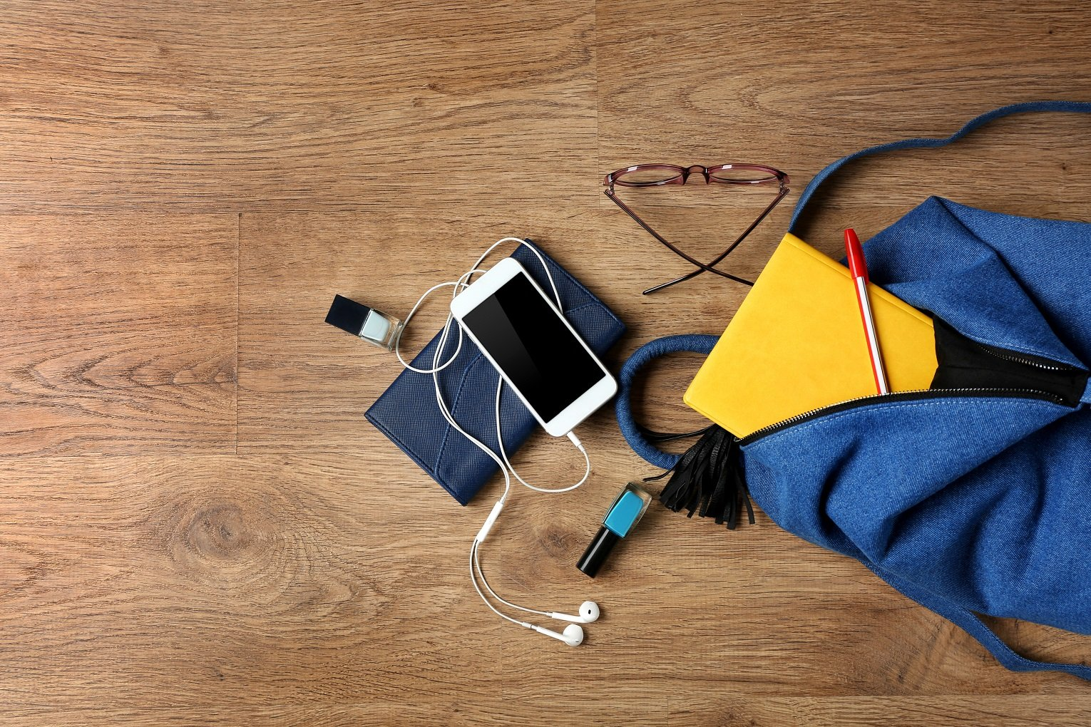 cell phone batteries backpack with accessories on wooden floor